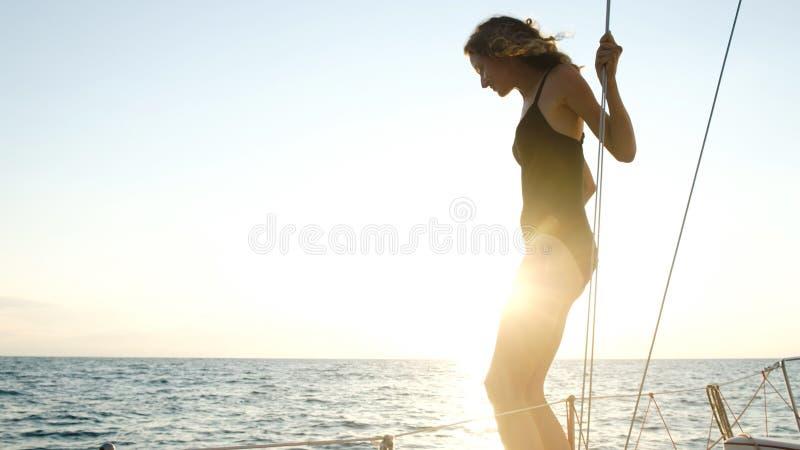 La muchacha delgada joven se está preparando para saltar de un yate navegante en el mar abierto en una puesta del sol fotografía de archivo