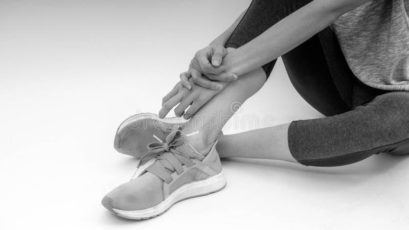 La muchacha deportiva blanca y negra, delgada se sienta cómodamente después de entrenamiento imagen de archivo libre de regalías