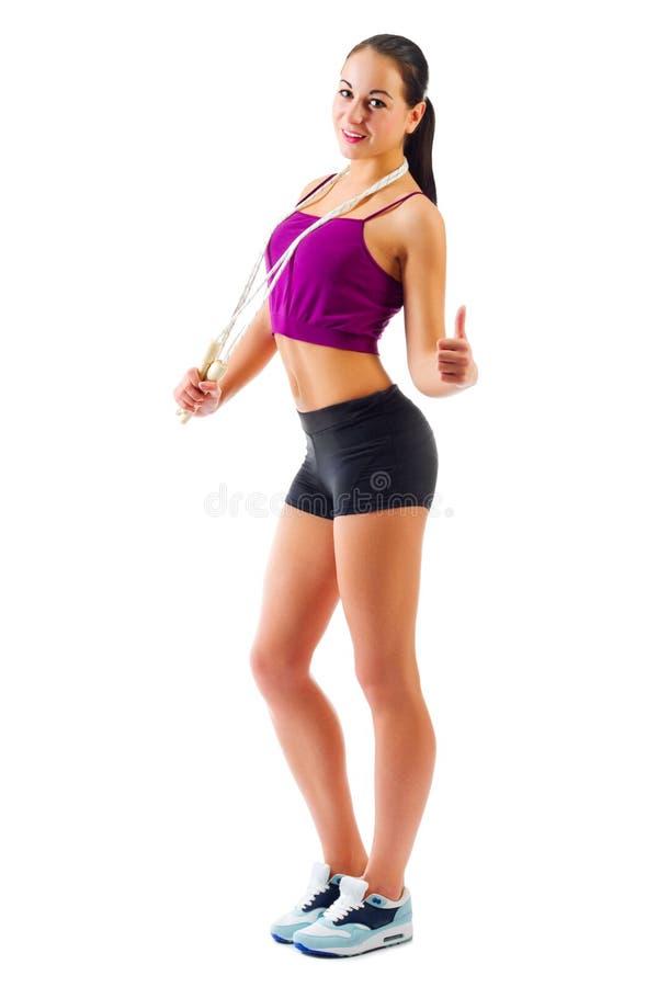 La muchacha deportiva joven con la cuerda que salta muestra gesto aceptable fotografía de archivo libre de regalías