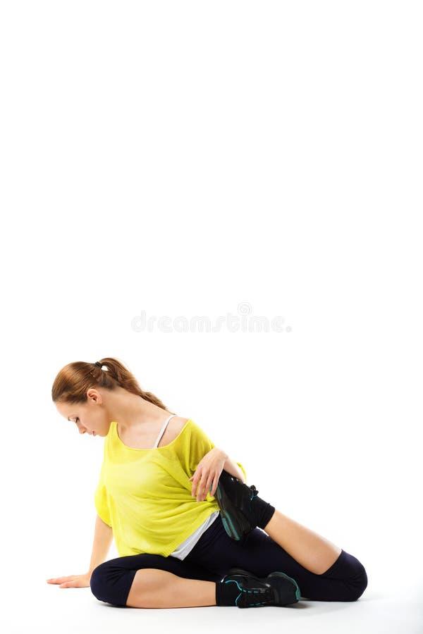 La muchacha deportiva joven que hace estirar ejercita sentarse en el piso imagenes de archivo
