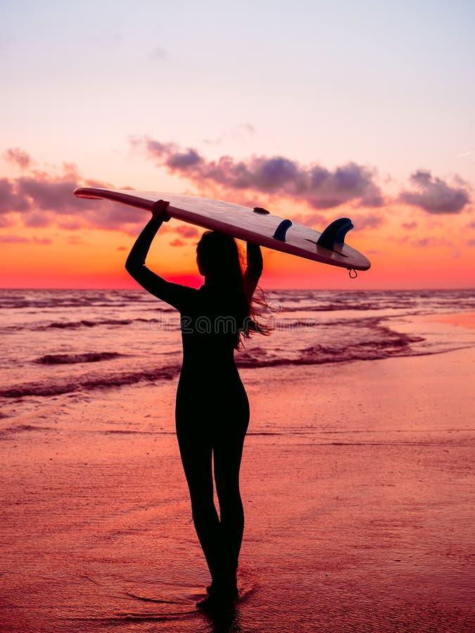 La muchacha deportiva va a practicar surf Mujer en wetsuit y puesta del sol o salida del sol roja en el océano foto de archivo