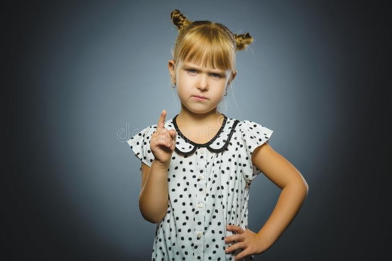 La muchacha descontentada y despectiva con amenaza al finger en fondo gris imágenes de archivo libres de regalías