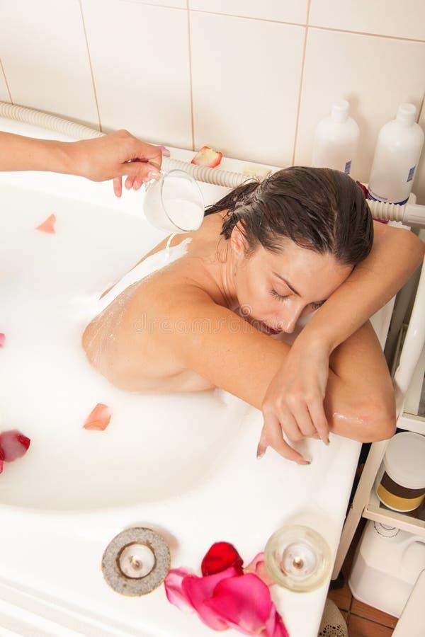 La muchacha descubierta atractiva disfruta de un baño con leche y pétalos color de rosa fotografía de archivo