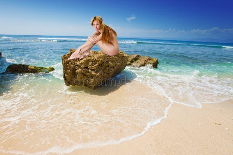 La muchacha descubierta en una piedra foto de archivo libre de regalías