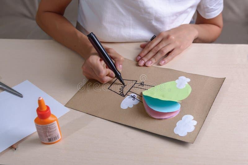 La muchacha dibuja con los creyones que se sientan en la tabla foto de archivo