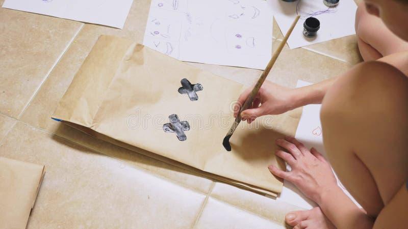 La muchacha dibuja con un cepillo en diversas emociones de las bolsas de papel El concepto de emociones en smiley fotografía de archivo