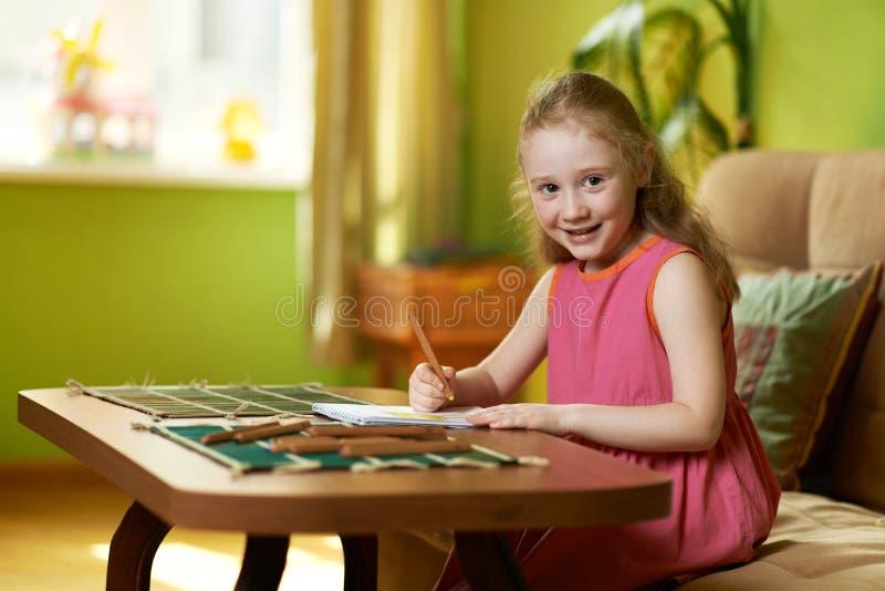 La muchacha dibuja el lápiz en el papel en la tabla foto de archivo