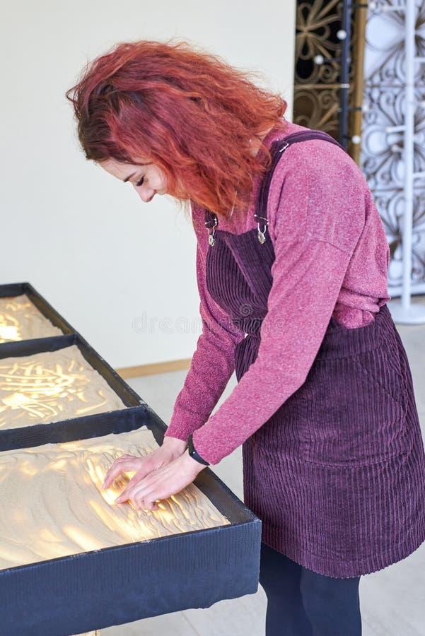 La muchacha dibuja en la arena con sus manos imágenes de archivo libres de regalías