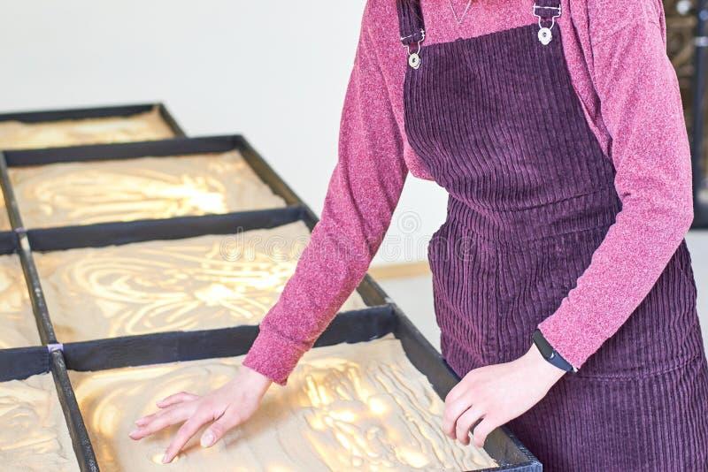 La muchacha dibuja en la arena con sus manos imagenes de archivo