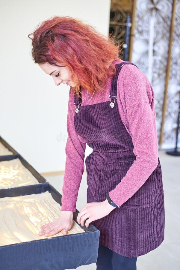 La muchacha dibuja en la arena con sus manos foto de archivo libre de regalías
