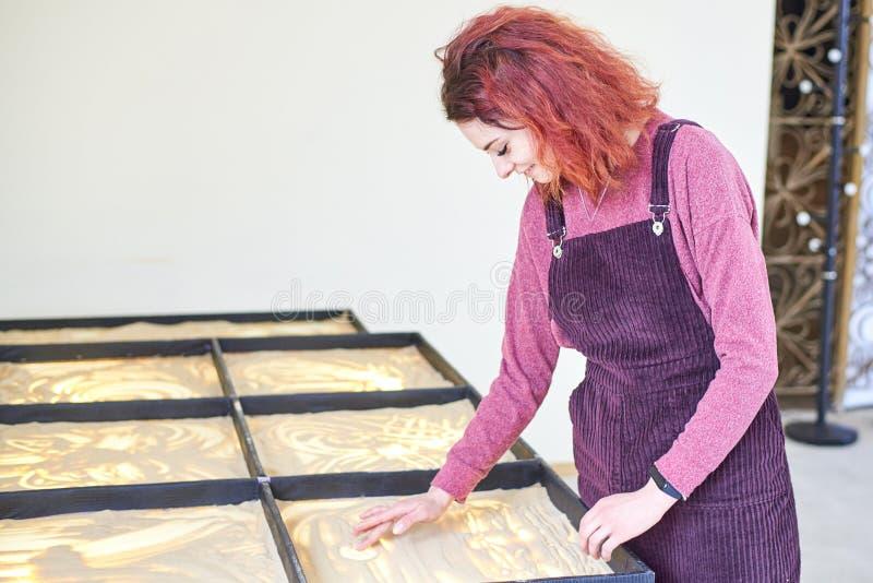 La muchacha dibuja en la arena con sus manos fotografía de archivo