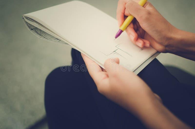 La muchacha dibuja en el papel, primer de las manos imagen de archivo libre de regalías