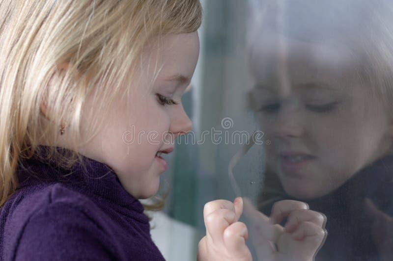 La muchacha dibuja en la ventana imágenes de archivo libres de regalías