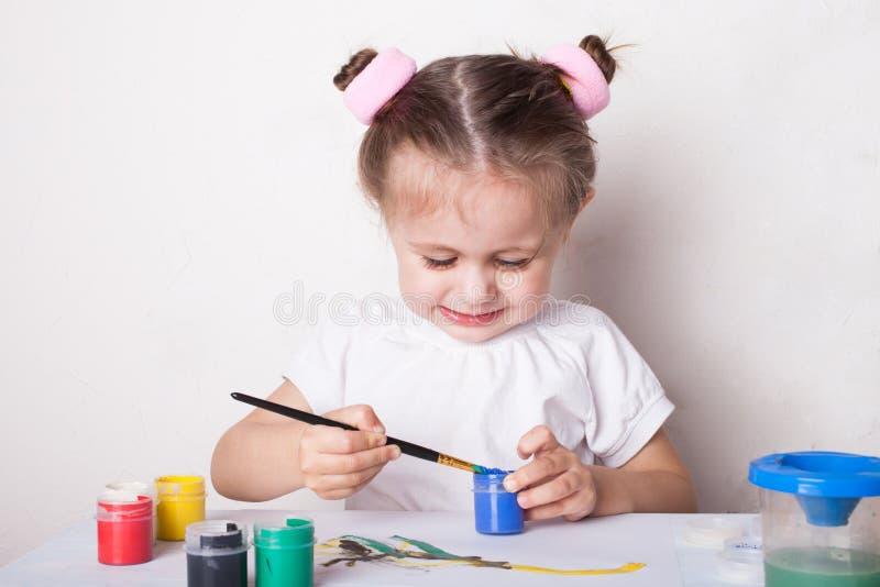 La muchacha dibuja en pinturas del color imagenes de archivo
