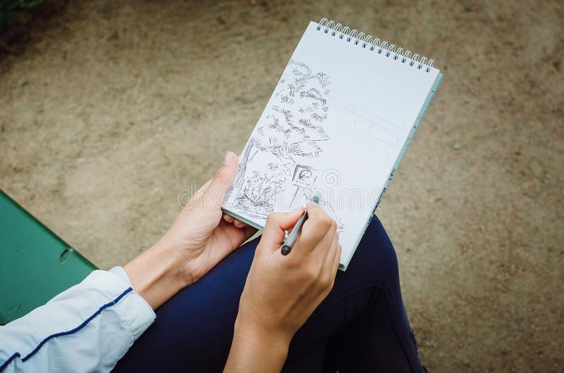 La muchacha dibuja en un cuaderno Da el primer stock de ilustración