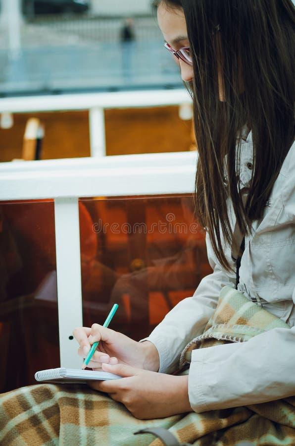 La muchacha dibuja en un cuaderno, foto vertical stock de ilustración
