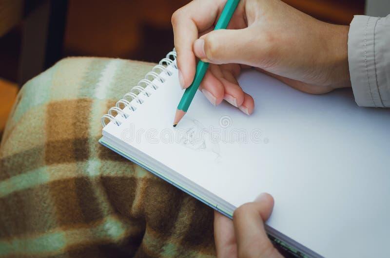 La muchacha dibuja en un cuaderno, primer stock de ilustración