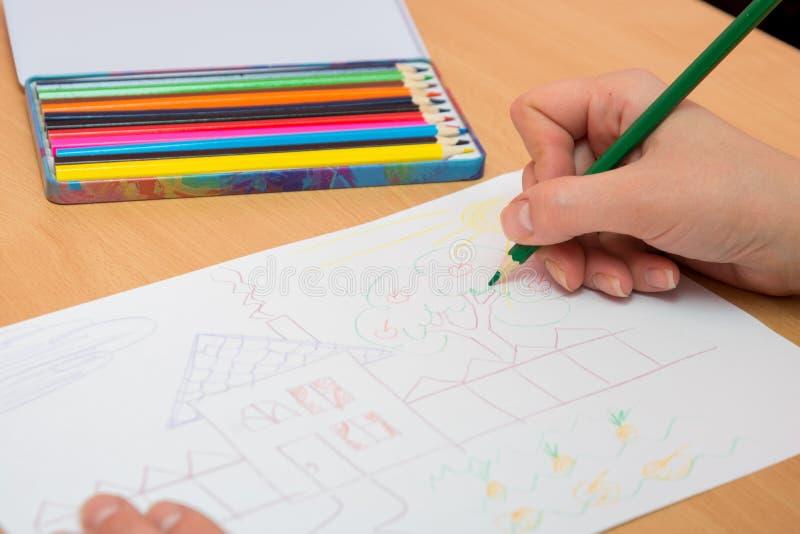 La muchacha dibuja la imagen con los lápices coloreados en el papel foto de archivo