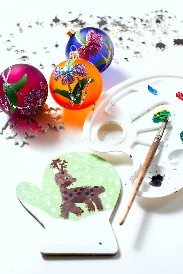 La muchacha dibuja las pinturas de los ciervos en la manopla de madera Regalo de la Navidad fotos de archivo