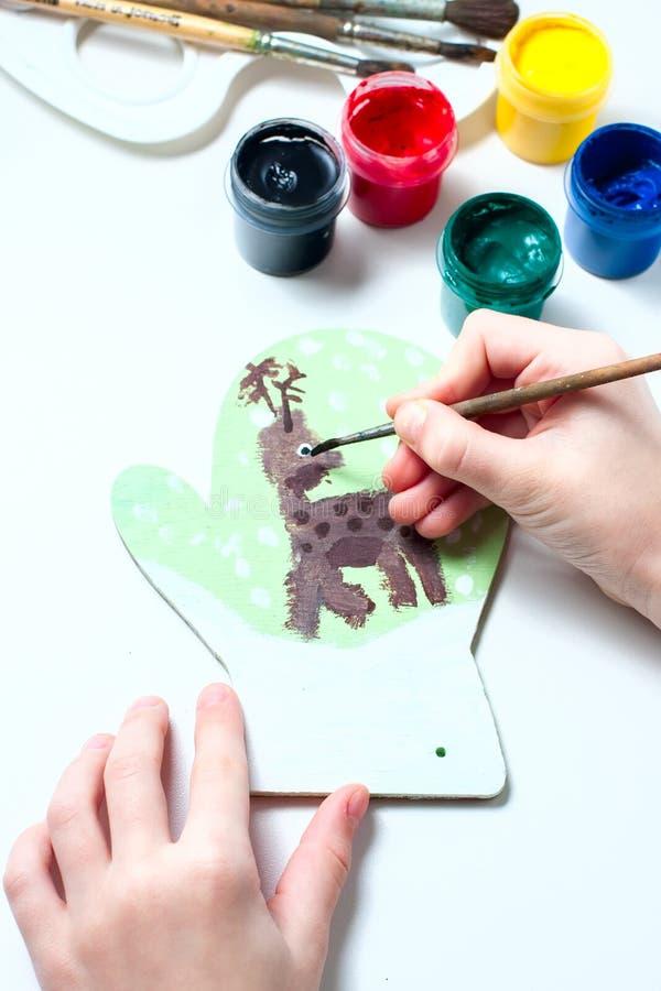 La muchacha dibuja las pinturas de los ciervos en la manopla de madera Regalo de la Navidad imagenes de archivo