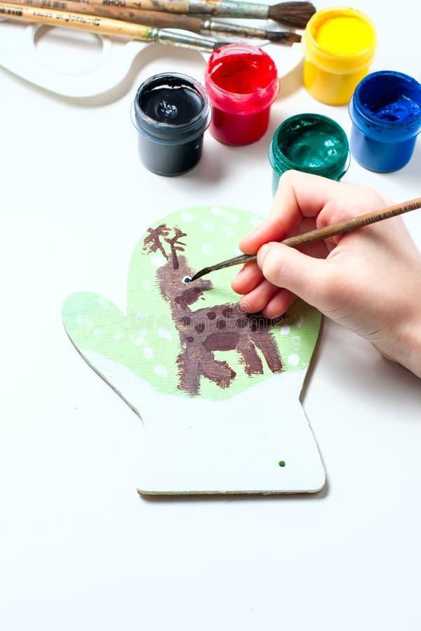 La muchacha dibuja las pinturas de los ciervos en la manopla de madera Regalo de la Navidad foto de archivo libre de regalías