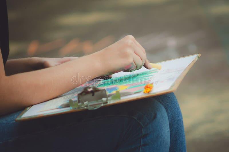 La muchacha dibuja los creyones en colores pastel en una tableta, primer foto de archivo