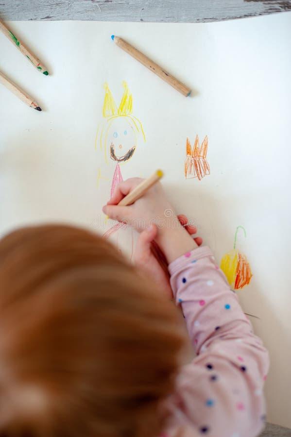 La muchacha dibuja a la princesa con los lápices coloreados fotos de archivo