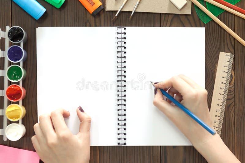 La muchacha dibuja un lápiz en un cuaderno imagen de archivo