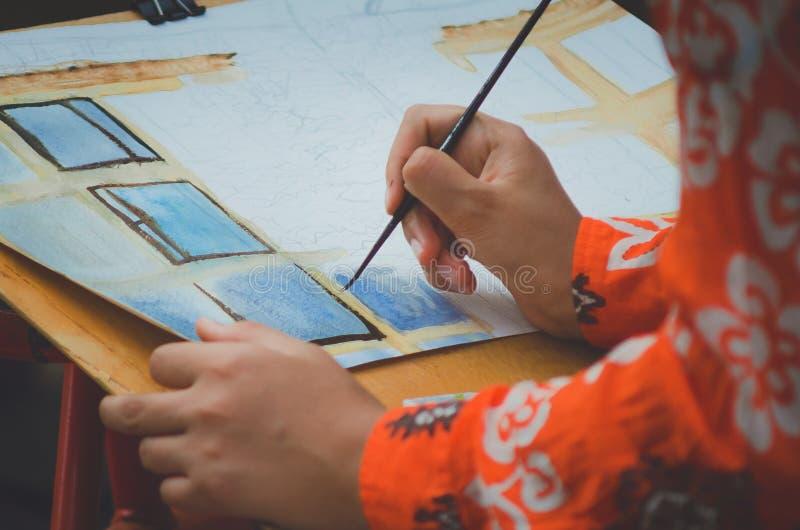 La muchacha dibuja una imagen con las acuarelas imagenes de archivo