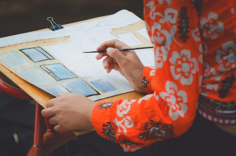La muchacha dibuja una imagen con las acuarelas fotos de archivo