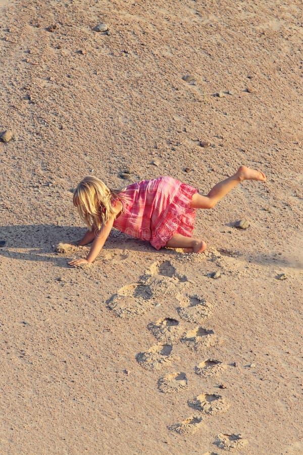 La muchacha divertida cae en vestido rojo de la montaña de la arena fotos de archivo