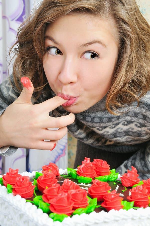 La muchacha divertida come la torta fotos de archivo libres de regalías