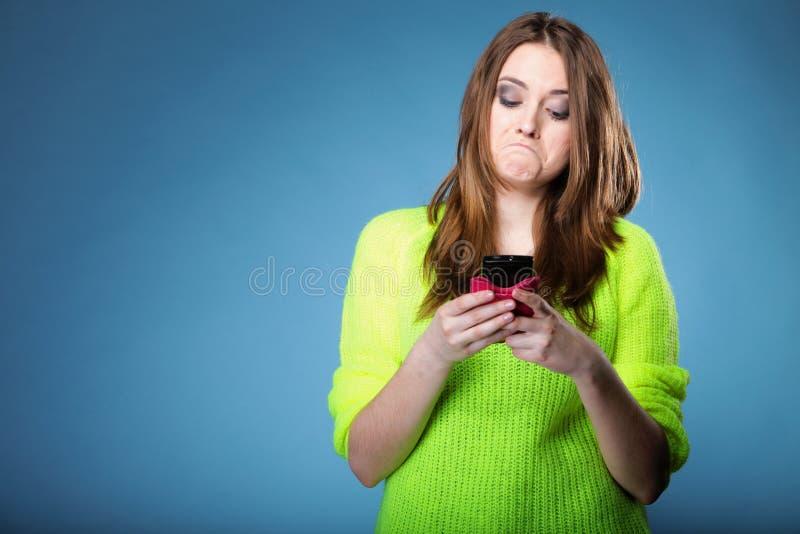 La muchacha divertida con el teléfono móvil lee el mensaje fotografía de archivo libre de regalías