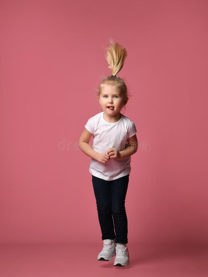 La muchacha divertida del ni?o corre y salta en fondo rosado imagenes de archivo