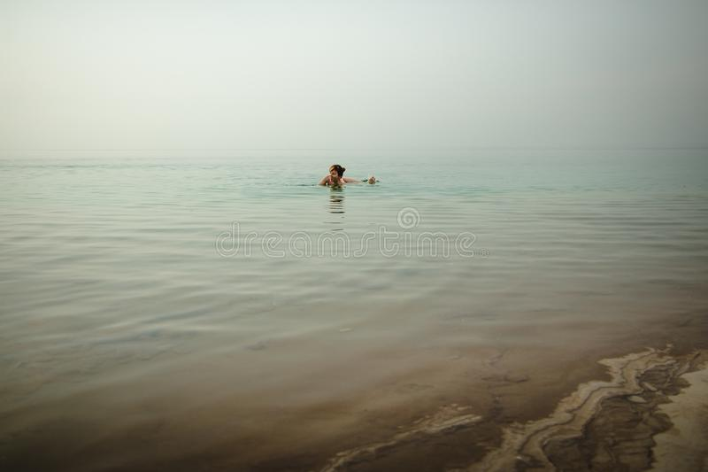 La muchacha divertida nada en agua del mar muerto en Jordania y niebla fotografía de archivo libre de regalías