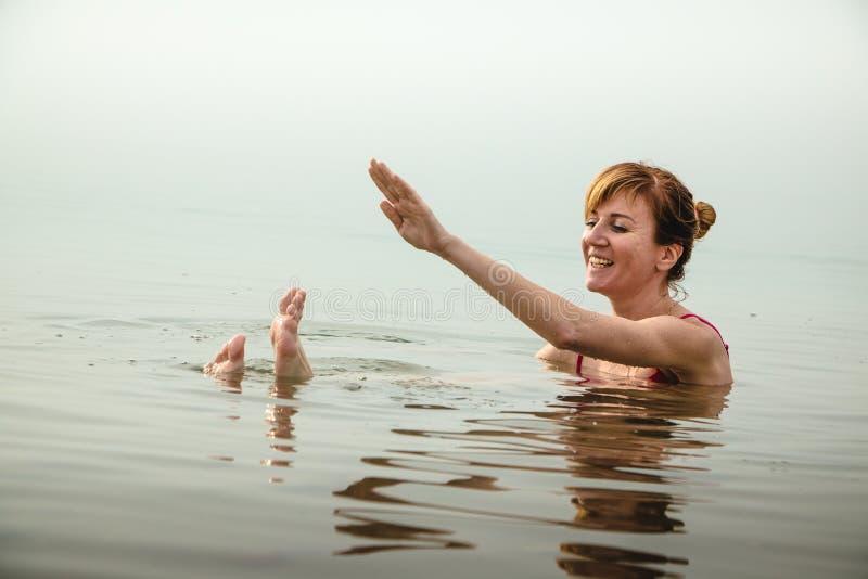 La muchacha divertida nada en agua del mar muerto en Jordania y niebla imagen de archivo