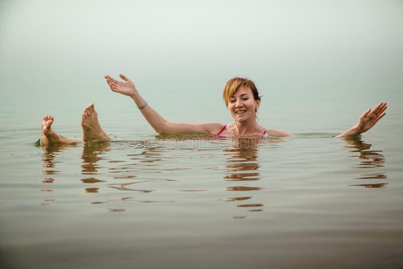 La muchacha divertida nada en agua del mar muerto en Jordania y niebla fotografía de archivo