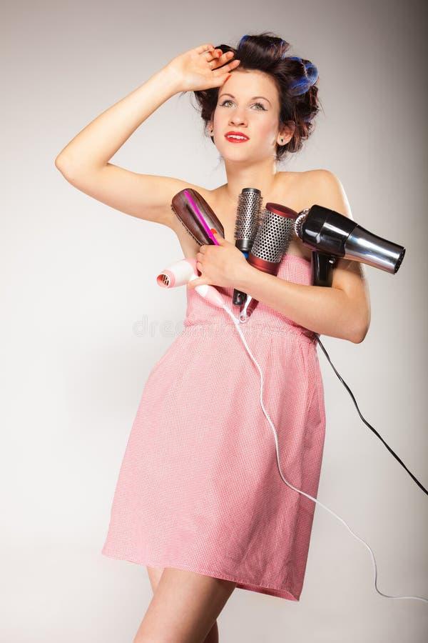 La muchacha divertida que diseña el pelo sostiene muchos accesorios fotos de archivo