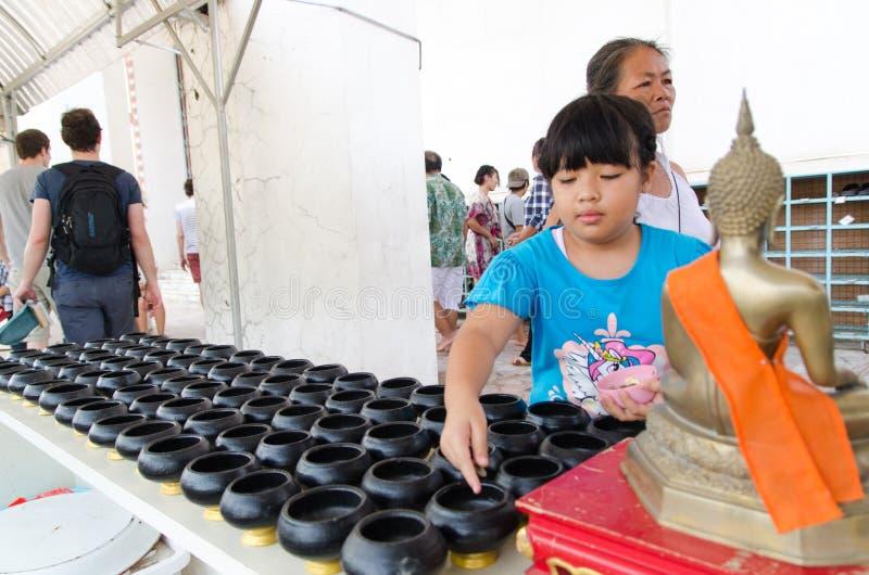 La muchacha dona el dinero para religioso foto de archivo libre de regalías