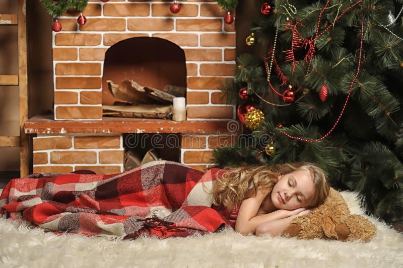 La muchacha duerme al lado de un árbol de navidad foto de archivo libre de regalías