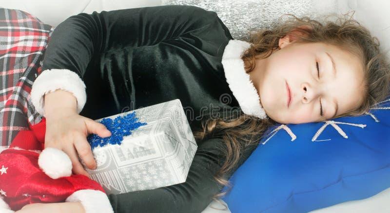 La muchacha duerme con el regalo de la Navidad imagen de archivo