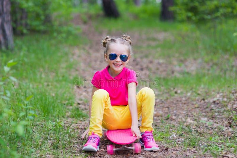 La muchacha dulce aprende montar un monopatín en el parque en el verano imagenes de archivo