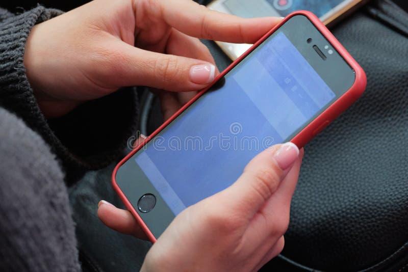 La muchacha durante la reunión utiliza un smartphone La mano de una mujer que sostiene un teléfono celular en un primer rojo del  fotos de archivo libres de regalías