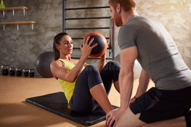 La muchacha ejercita los músculos del ABS usando bola imagenes de archivo