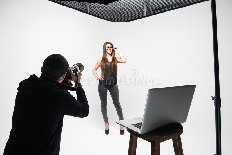 La muchacha el fotógrafo toma imágenes del modelo en negro en un fondo blanco imágenes de archivo libres de regalías