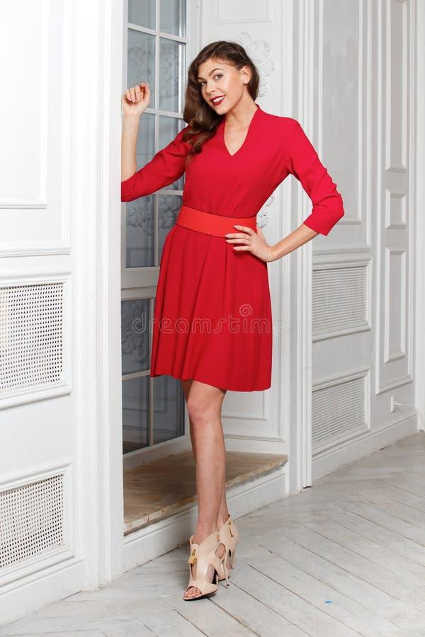 La muchacha elegante magn?fica vestida en el vestido rojo de moda presenta en el cuarto al lado de la puerta blanca fotos de archivo libres de regalías