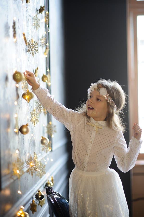 La muchacha elegante vestida de 8-9 años con placer toca las guirnaldas de la Navidad del oro imagen de archivo