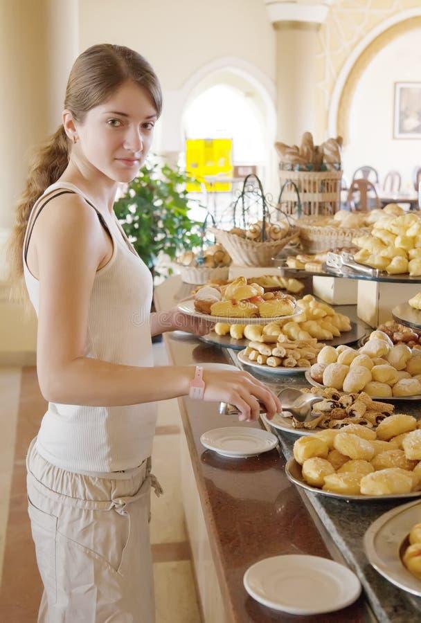 La muchacha elige la comida dulce fotografía de archivo
