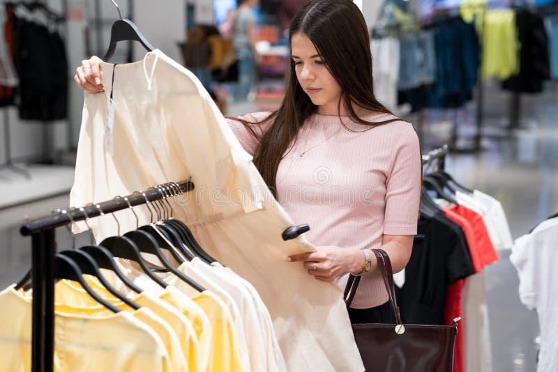 La muchacha elige la ropa en la tienda imagenes de archivo