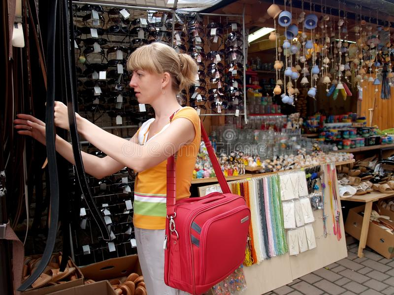 La muchacha elige una correa de cuero en un banco de la mercería fotos de archivo